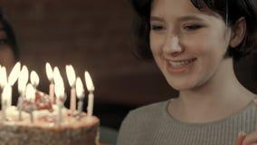 La muchacha atractiva joven está a punto de hacer un deseo y soplar todas las velas Imagen de archivo libre de regalías