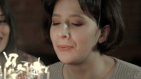 La muchacha atractiva joven está a punto de hacer un deseo y soplar todas las velas almacen de video