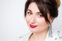 La muchacha atractiva joven hermosa de la mujer, empresaria en la chaqueta elegante blanca, se adapta al lápiz labial del rojo de Fotografía de archivo
