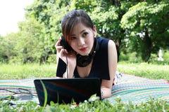 La muchacha atractiva joven se está relajando en el parque Foto de archivo libre de regalías