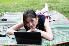 La muchacha atractiva joven se está relajando en el parque Fotos de archivo libres de regalías