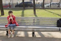 La muchacha atractiva joven se está sentando en el banco Fotos de archivo libres de regalías
