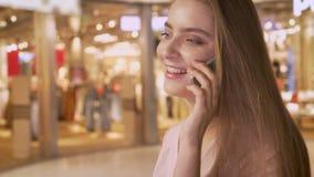 La muchacha atractiva joven va a hacer compras en alameda, hablando en el teléfono, concepto que hace compras, concepto de la mod metrajes