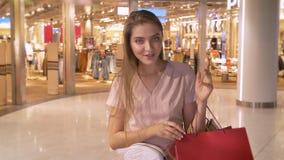 La muchacha atractiva joven va a hacer compras en la alameda, relojes en los bolsos, sorpresa expresa, concepto que hace compras, metrajes