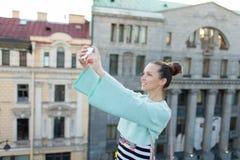La muchacha atractiva linda con el pelo marrón se coloca en el tejado de la casa en la ciudad vieja y hace un selfie en su smartp Foto de archivo