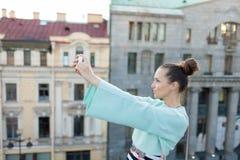 La muchacha atractiva linda con el pelo marrón se coloca en el tejado de la casa en la ciudad vieja y hace un selfie en su smartp Fotos de archivo