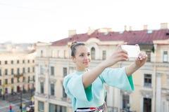 La muchacha atractiva linda con el pelo marrón se coloca en el tejado de la casa en la ciudad vieja y hace un selfie en su smartp Imagen de archivo
