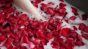 La muchacha atractiva miente en un baño de piedra grande con una flor color de rosa en sus manos metrajes