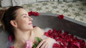 La muchacha atractiva miente en un baño de piedra grande con una flor color de rosa en sus manos almacen de video