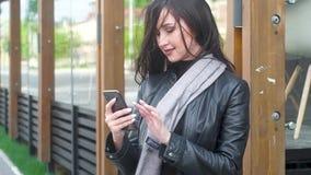 La muchacha atractiva mira el teléfono, presiona los botones el pelo se está convirtiendo en viento almacen de metraje de vídeo