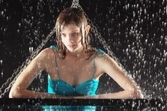 La muchacha atractiva mojada se inclinó en el oscilación con los encadenamientos Foto de archivo