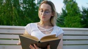 La muchacha atractiva que lee un libro en el banco y quita el pelo de su cara metrajes