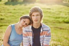 La muchacha atractiva que se inclina en el hombro de su novio que la cierra los ojos con el enjoyong del placer junta calma la at Imagen de archivo