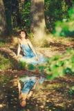 La muchacha atractiva que se sienta en el banco del lago Foto de archivo libre de regalías