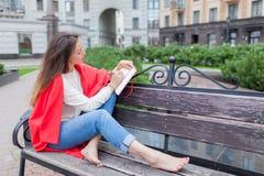La muchacha atractiva que se sienta en un banco con los pies desnudos, cubiertos con una manta roja, en la nueva área residencial Foto de archivo libre de regalías
