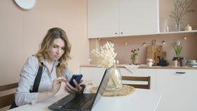 La muchacha atractiva rubia paga una compra en Internet a trav?s de un tel?fono m?vil en casa almacen de video