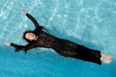 La muchacha atractiva se baña en piscina Imagen de archivo