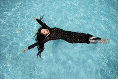 La muchacha atractiva se baña en piscina Fotografía de archivo libre de regalías
