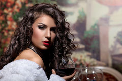 La muchacha atractiva se sienta con el vino en abrigo de pieles en la tarde Imagenes de archivo