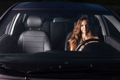 La muchacha atractiva se sienta detrás de la rueda del coche y hace caras al aire libre Foto de archivo