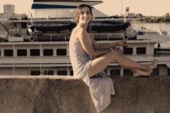 La muchacha atractiva se sienta y mirando para arriba en el fondo de la nave Fotos de archivo