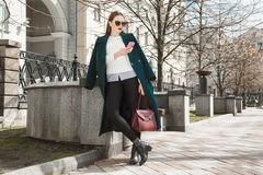 La muchacha atractiva se vistió en una capa costosa, un suéter blanco y gafas de sol con un teléfono móvil en su presentación de  imágenes de archivo libres de regalías