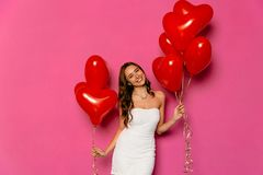 La muchacha atractiva sostiene los globos en dos manos el día del ` s de la tarjeta del día de San Valentín Imagenes de archivo