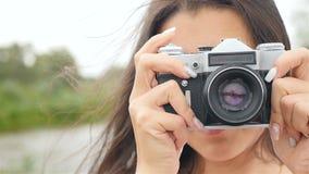 La muchacha atractiva toma imágenes en la cámara retra Primer metrajes