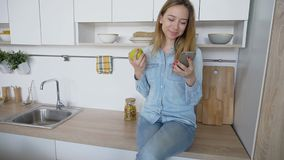 La muchacha atractiva utiliza el teléfono elegante y come la manzana, sentándose en kitc foto de archivo
