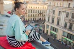 La muchacha atractiva y elegante se sienta en el tejado de la casa en la ciudad vieja y lee el eBook Fotografía de archivo