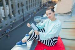 La muchacha atractiva y elegante se sienta en el tejado de la casa en la ciudad vieja y lee el eBook Foto de archivo