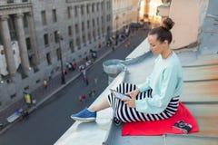 La muchacha atractiva y elegante se sienta en el tejado de la casa en la ciudad vieja y lee el eBook Ella se sienta en una manta  Fotos de archivo libres de regalías