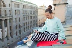 La muchacha atractiva y elegante se sienta en el tejado de la casa en la ciudad vieja y lee el eBook Ella se sienta en una manta  Fotos de archivo