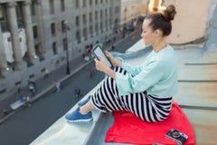 La muchacha atractiva y elegante se sienta en el tejado de la casa en la ciudad vieja y lee el eBook Ella se sienta en una manta  Foto de archivo libre de regalías