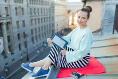 La muchacha atractiva y elegante se sienta en el tejado de la casa en la ciudad vieja y lee el eBook Ella se sienta en una manta  Imagenes de archivo