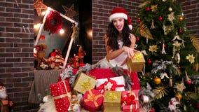 La muchacha atractiva y muchos regalos de la Navidad, muchacha linda de Santa Claus, elige un regalo para usted, presentación del almacen de video