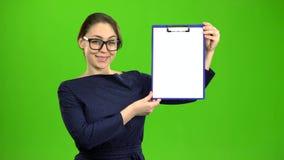 La muchacha aumenta una tableta de papel y sonríe Pantalla verde almacen de metraje de vídeo