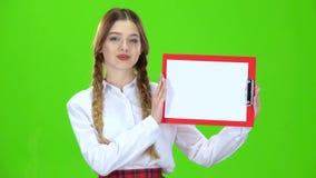 La muchacha aumenta una tableta roja con el papel Pantalla verde almacen de metraje de vídeo