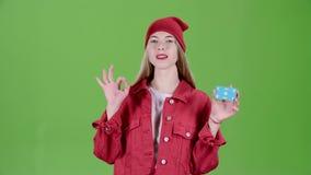 La muchacha aumenta una tarjeta azul y muestra los pulgares para arriba y muestra muy bien Pantalla verde almacen de metraje de vídeo