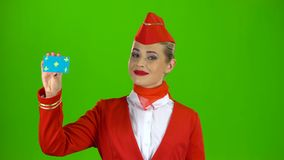 La muchacha aumenta una tarjeta y muestra a puntos una mano en ella Pantalla verde almacen de metraje de vídeo