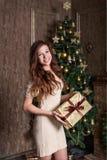 la muchacha auténtico alegre que sonríe con un regalo de Navidad en sus manos se está colocando en un vestido clásico del vintage Fotografía de archivo libre de regalías
