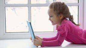 La muchacha avanzada en un vestido rosado se está sentando por la ventana con una tableta imagen de archivo