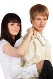 La muchacha ayuda al hombre a vestir el juego del día de fiesta Fotos de archivo libres de regalías
