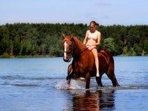 La muchacha baña el caballo en el lago Fotos de archivo