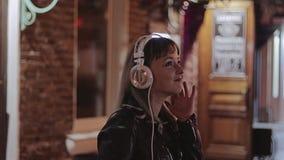 La muchacha baila en la noche en la calle que escucha la música en los auriculares metrajes