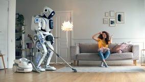 La muchacha baila mientras que un vacío del droid limpia almacen de metraje de vídeo