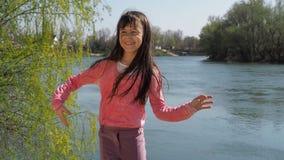 La muchacha baila por el agua Niño en un día soleado en el aire fresco El viento desarrolla el pelo Una niña está bailando en el  metrajes