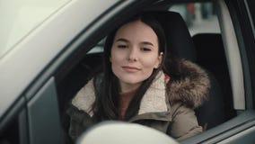 La muchacha baja el vidrio en la puerta de su coche metrajes