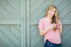 La muchacha bastante adolescente canta y escucha la música en el teléfono elegante Foto de archivo