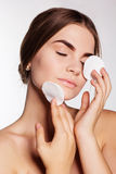 La muchacha bastante adolescente está limpiando la cara con algodón Imagen de archivo